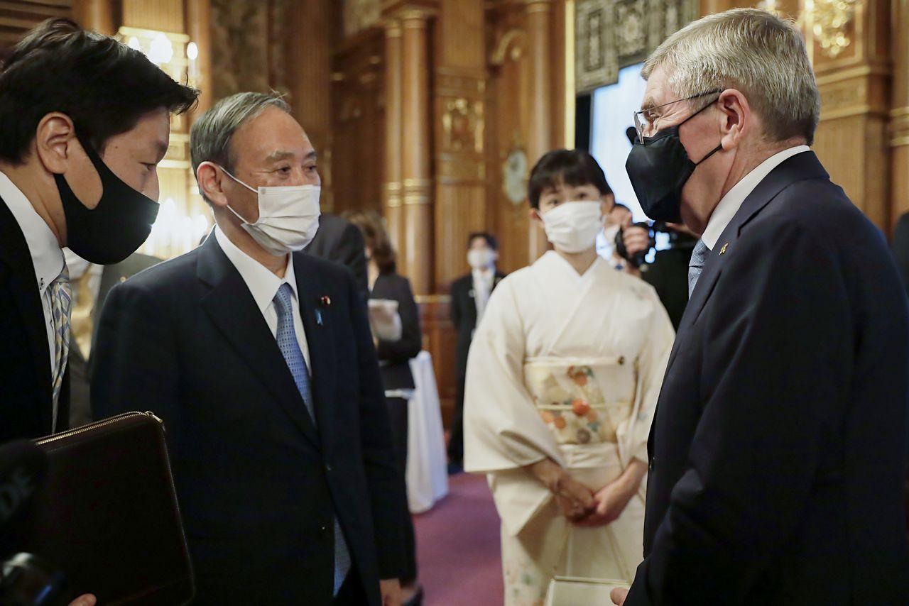 日本首相菅義偉(左2)與國際奧會(IOC)主席巴赫在東京奧組委舉辦的歡迎晚會上交談(右1)18日下午於東京元赤阪迎賓館(Photo by Tokyo 2020,時事)