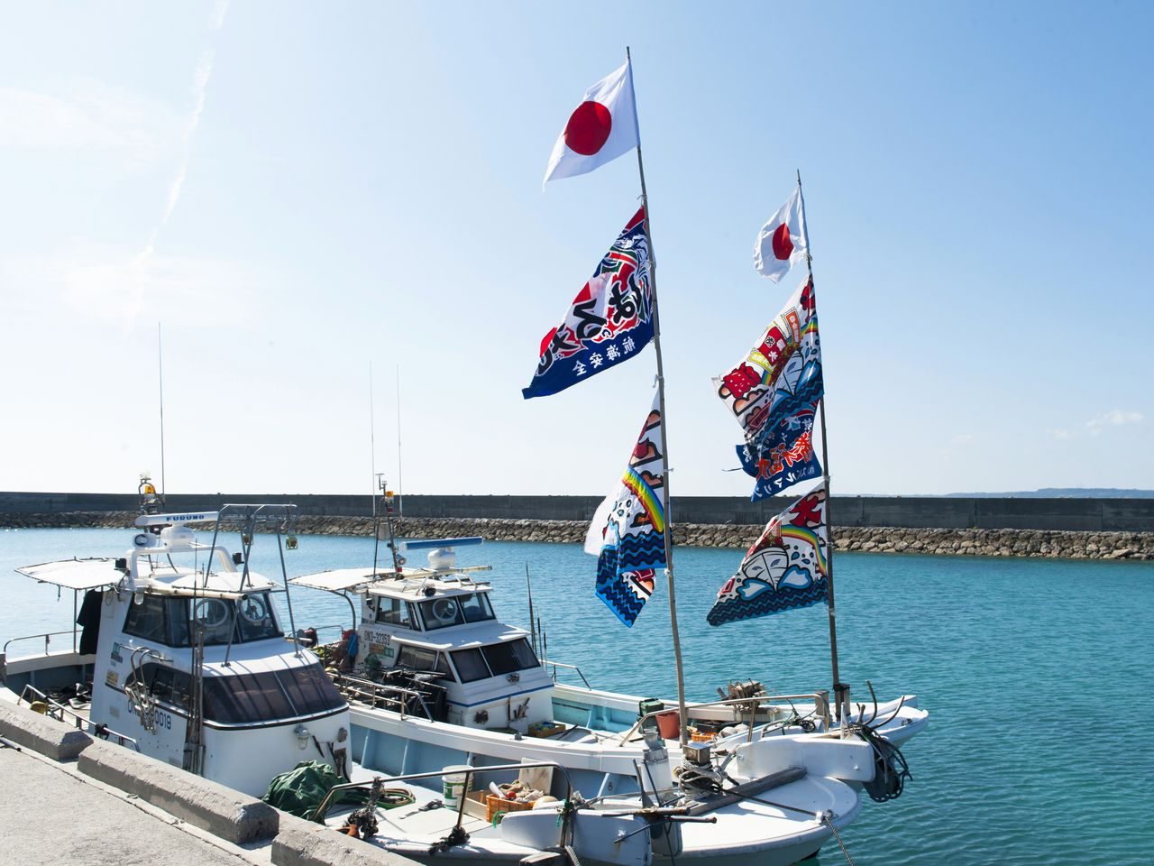 Fishing boats moored at a fishing port display colorful <em>tairyōbata</em> banners.