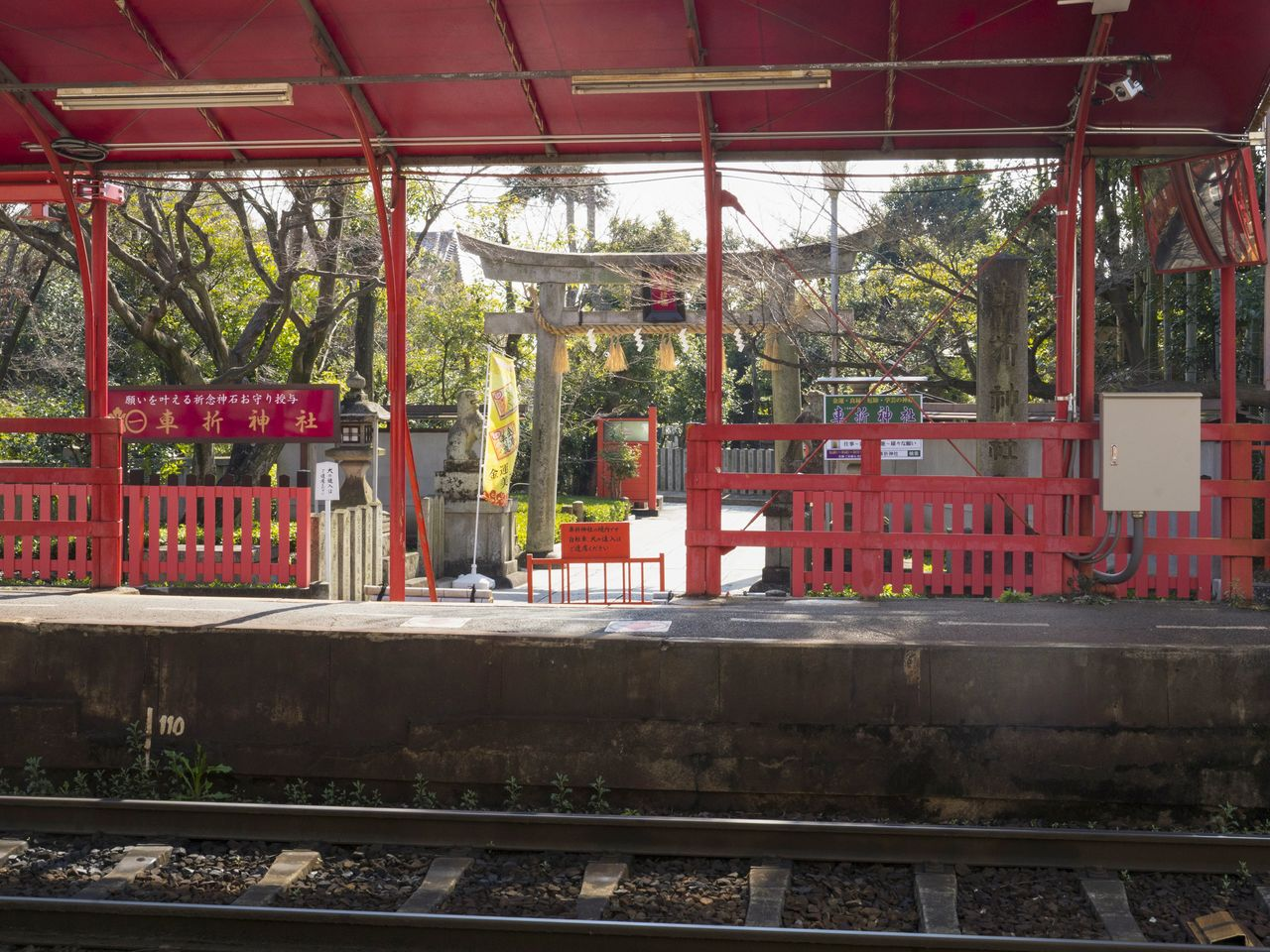 The torii at the rear approach to the shrine is visible from the platform of the Randen Kurumazaki-jinja Station.