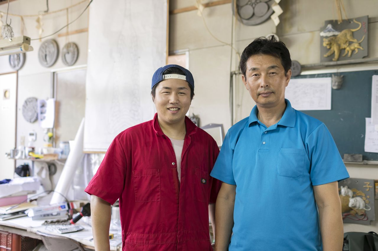 Fujimoto Kōsuke (right) and his son Shūgo at the Fujimoto Onigawara workshop, where work on the shachihoko sculptures is underway. (© Odasaki Tomohiro; all rights reserved)