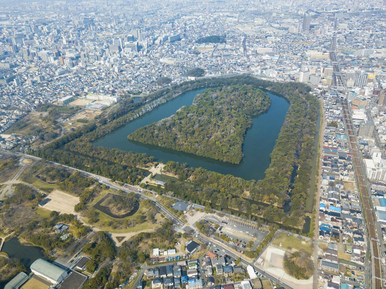 The Emperor Nintoku Burial Mound has three concentric moats. To the south of the site, in the lower part of the photo, is Daisen Park, which abuts the larger burial mound site.