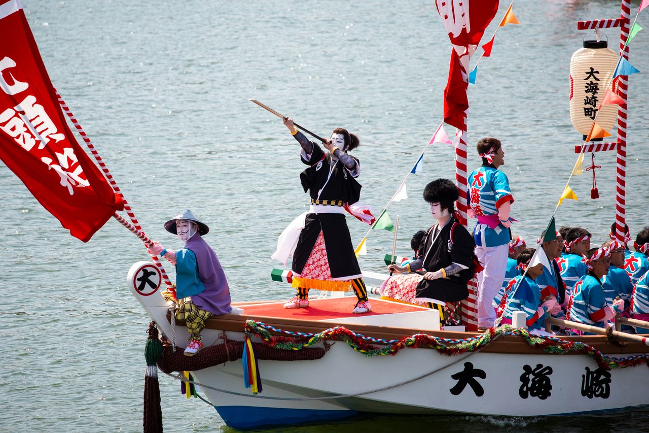 The <em>kengai</em> are themselves dressed in a variety of costumes. The Ōmisaki crew stand out among the gaudy colors of others' costumes with their more restrained, basic black look.