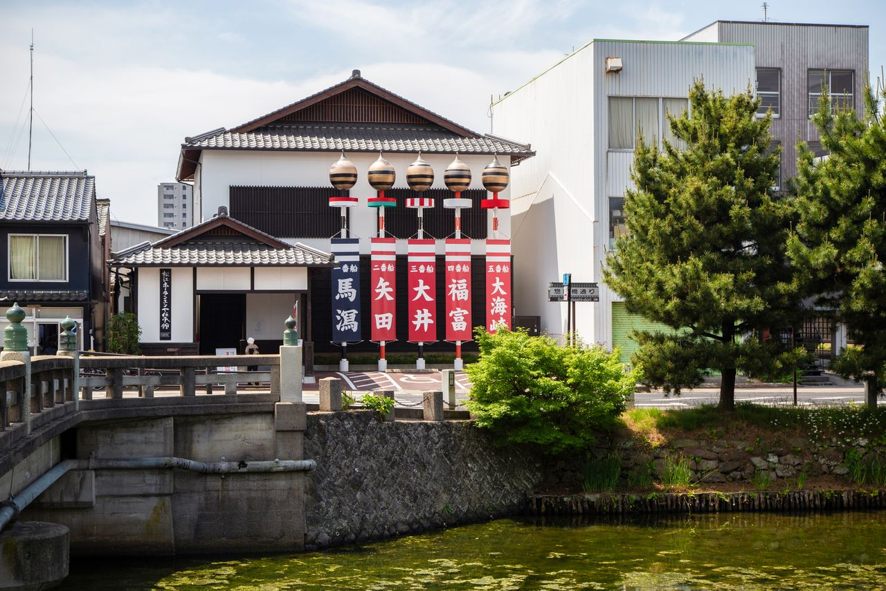 The Hōran En'ya Memorial Hall, near the Hori River, is marked by banners of the Five Lands to welcome visitors.