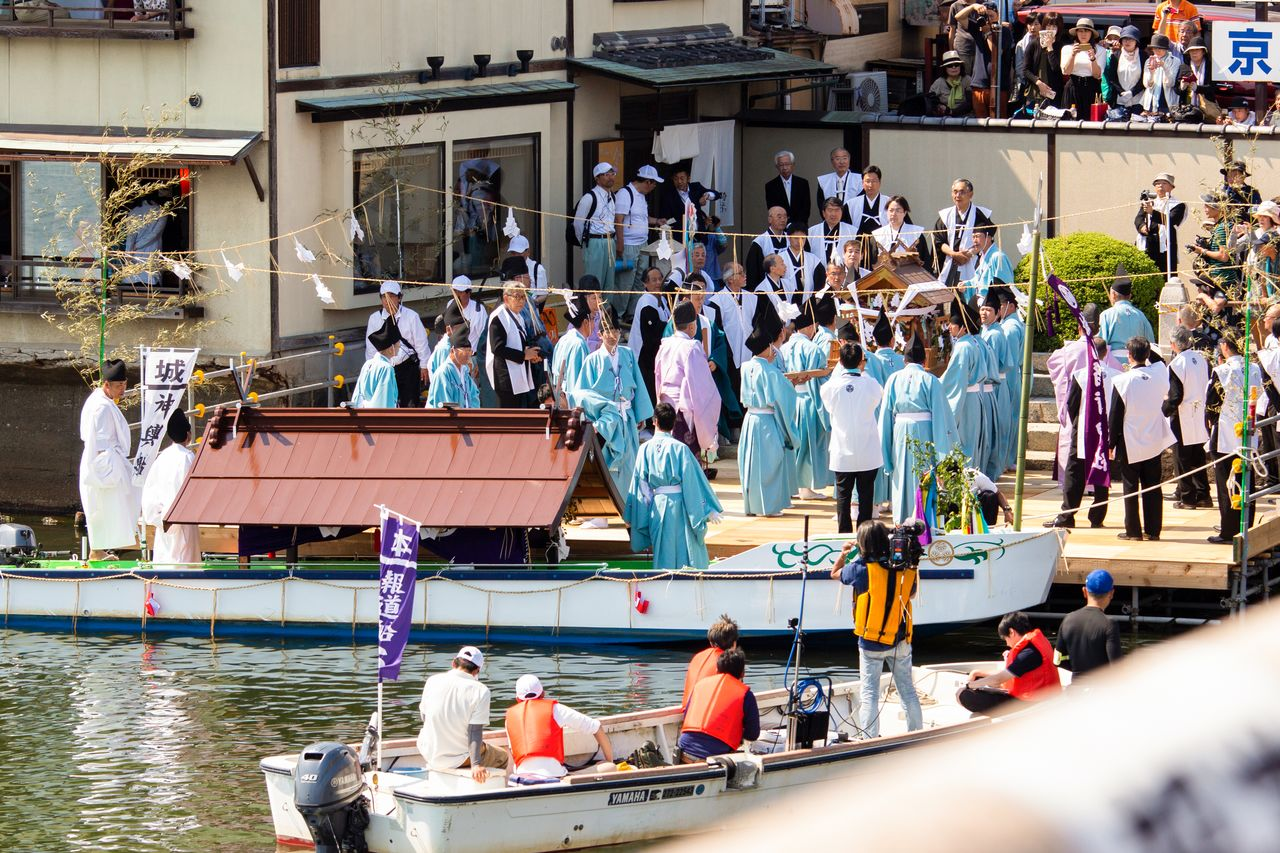 The casket of the spirits is transferred from the boat to the land at the Kitazume jetty of the Matsue Bridge.