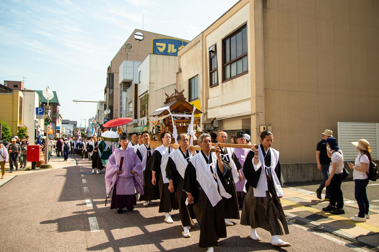 The casket of spirits is carried through the castle town of Matsue.