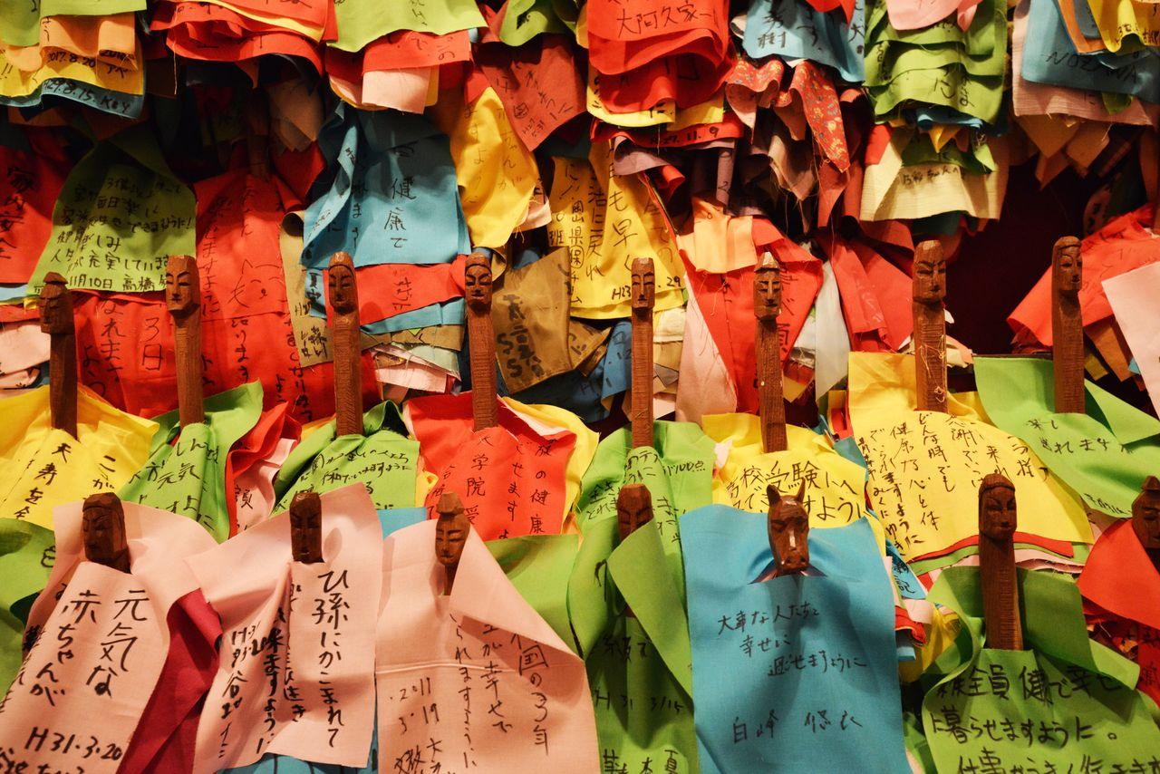 Wood-carved figurines are covered with prayers written on cloth.