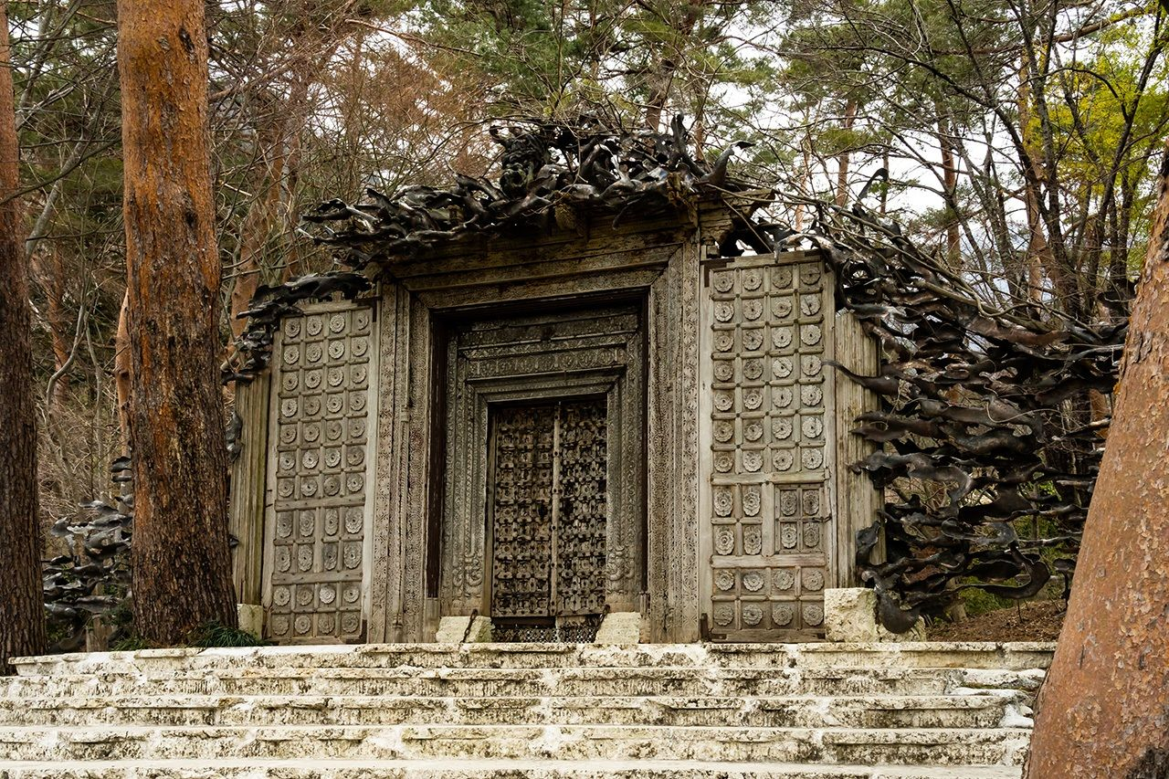 The main entrance to the museum features a carved wooden door Itchiku bought on a visit to India. Musasabi, Japanese flying squirrels, nest in the branches along the top of its frame.