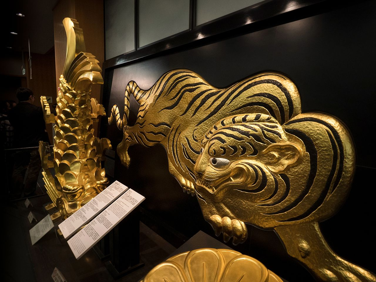 A golden <em>shachihoko</em> roof ornament and tiger are displayed on the second floor.