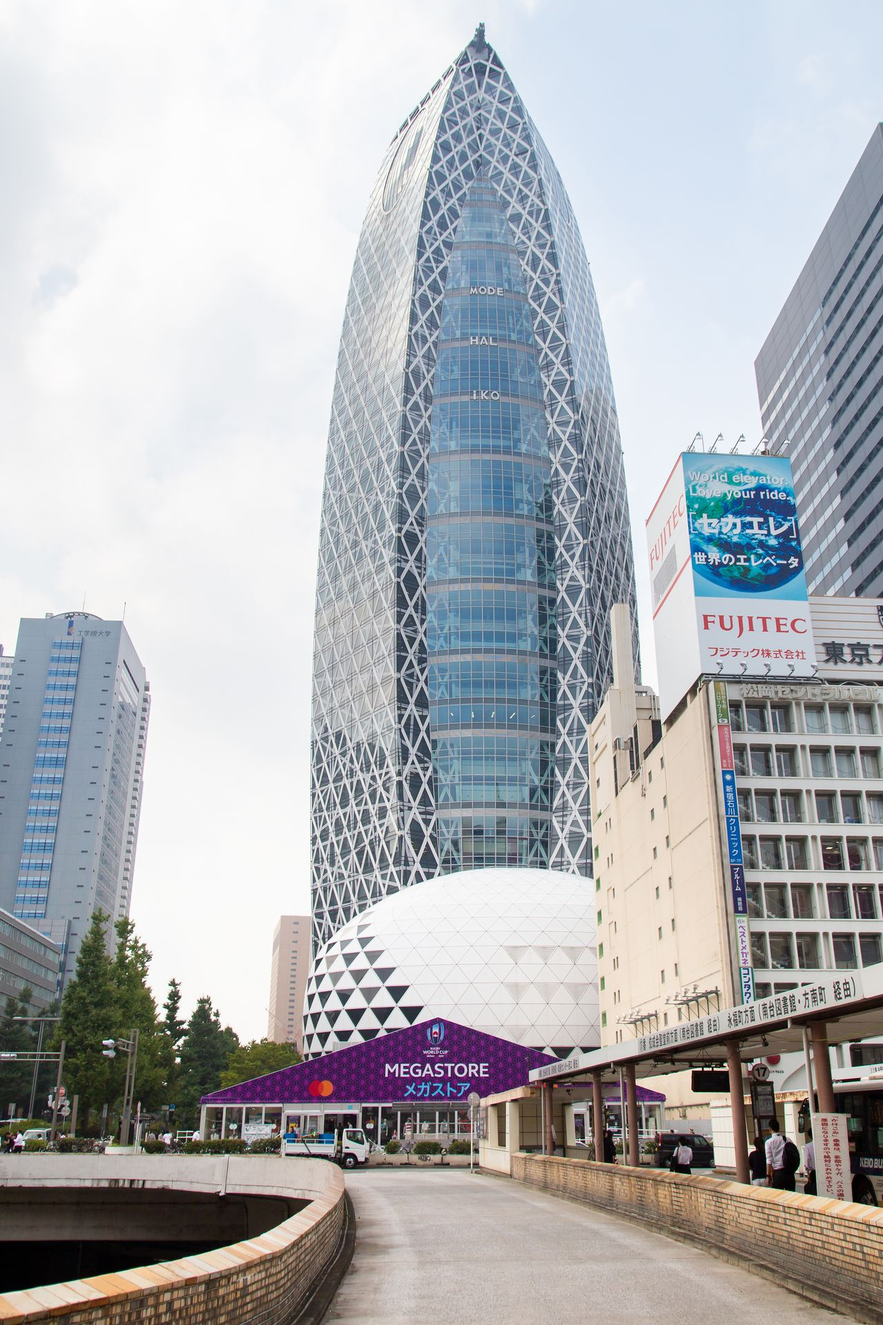 The Rugby World Cup Megastore is visible from the west exit of Shinjuku Station. The cocoon-like Mode Gakuen tower is a handy landmark.