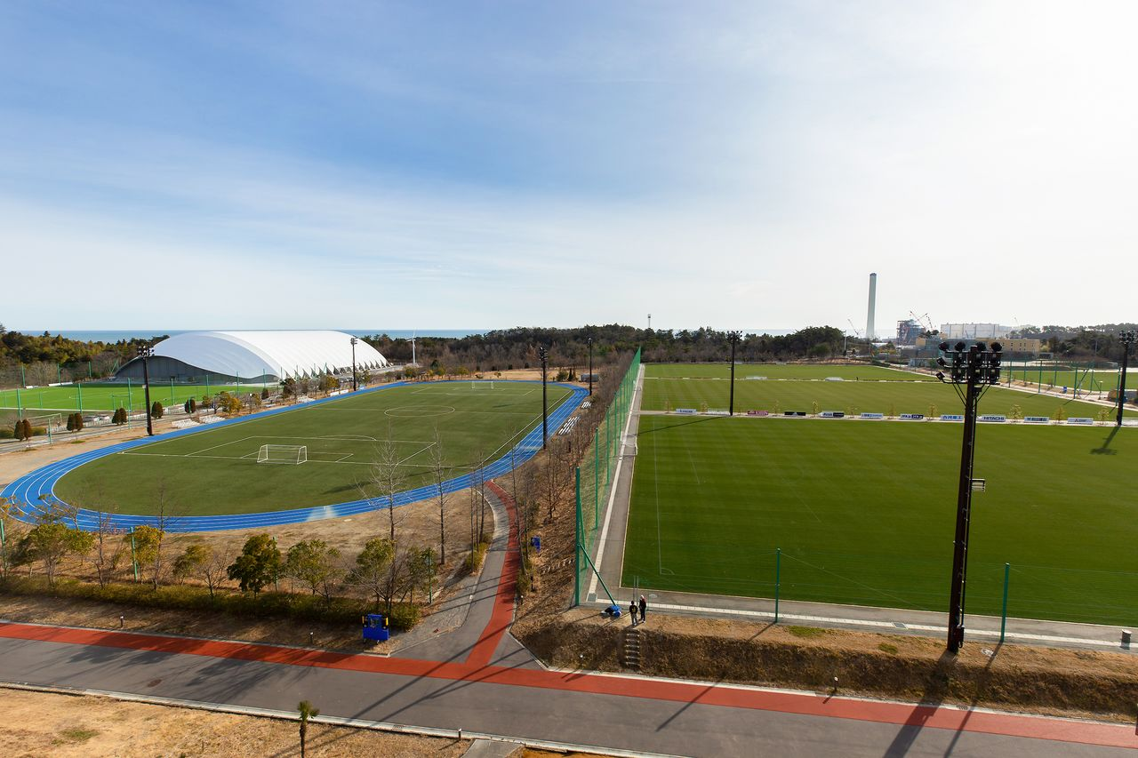 Soccer grounds at the J-Village. The three pitches to the right are natural grass and the oval ground to the left is synthetic turf. The Pacific Ocean can be seen beyond the covered all-weather practice facility in the background.