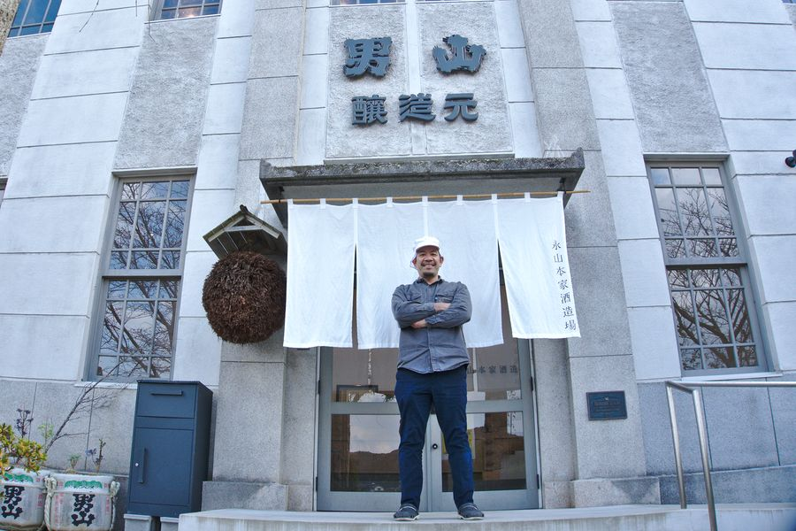 Nagayama Takahiro in front of his brewery. To the left of the noren curtain is a sugitama, a ball of cedar branches traditionally hung at the entrance of a sake brewery to mark the production of a new batch from the year's rice harvest.