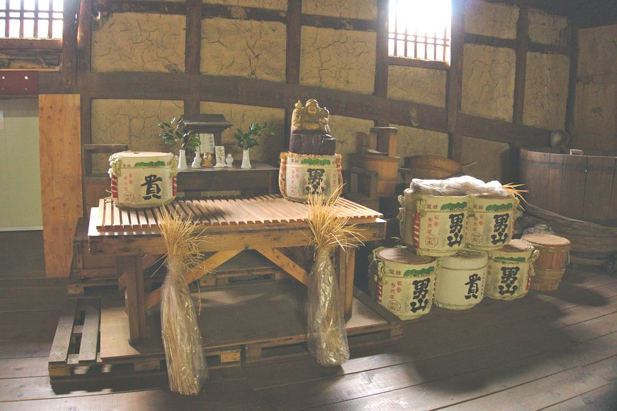Casks of sake are placed with sheaves of locally harvested rice before the brewery's altar.