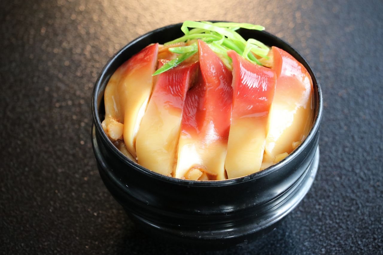 A bowl of hokki meshi topped with sliced negi onions. (© Pixta)