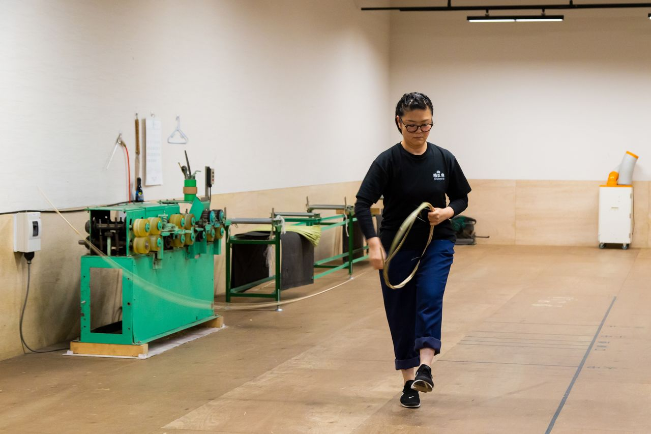 With dance-like movements, trainee Arai Chika demonstrates how to wind the bamboo for making a barrel hoop.