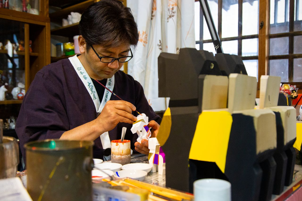 Hashimoto in a corner of his shop, painting a design onto a Miharu-goma figure.