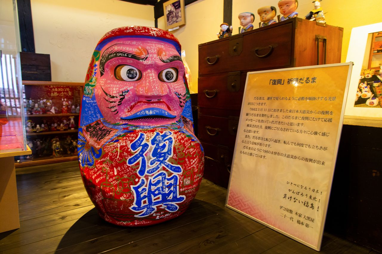 "The ""Pray for Reconstruction"" daruma, covered in messages praying for the revival of the devastated Tōhoku region."