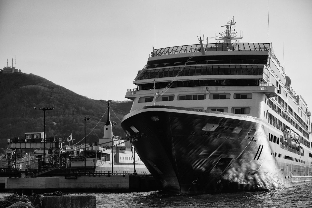 A 30,000-ton-class cruise liner arrives at the Machinaka (City Center) Dock, which is indeed right beside JR Hakodate Station and the Hakodate Morning Market. Looming into frame from the left is the summit of Mount Hakodate (2019).