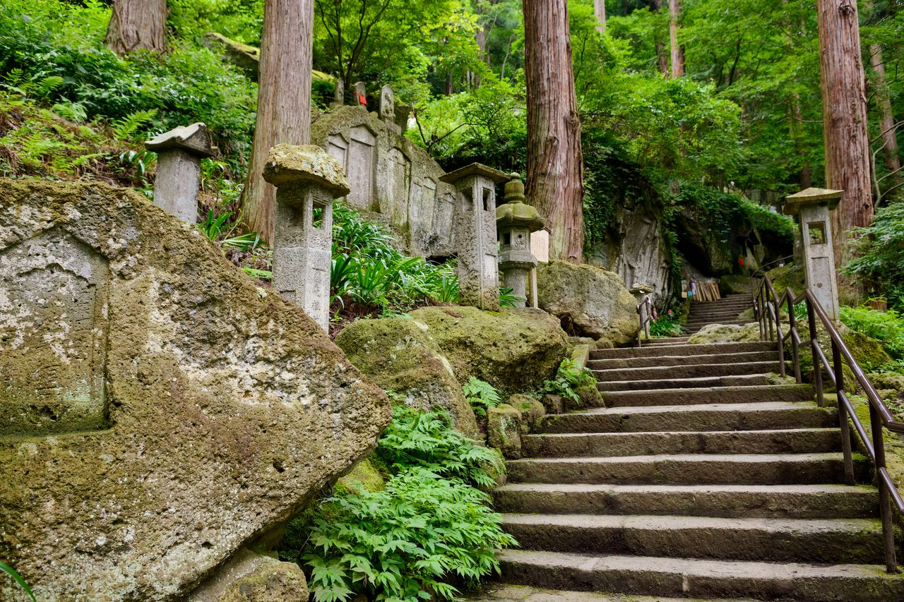Stone steps leading up the mountain weave through a dense forest. (Courtesy of the Yamagata Tourist Association)