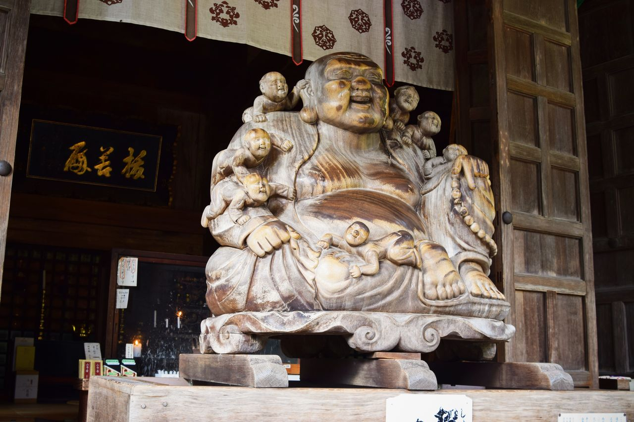 The belly of Hotei, one of the seven gods of fortune, has been rubbed smooth by worshippers.