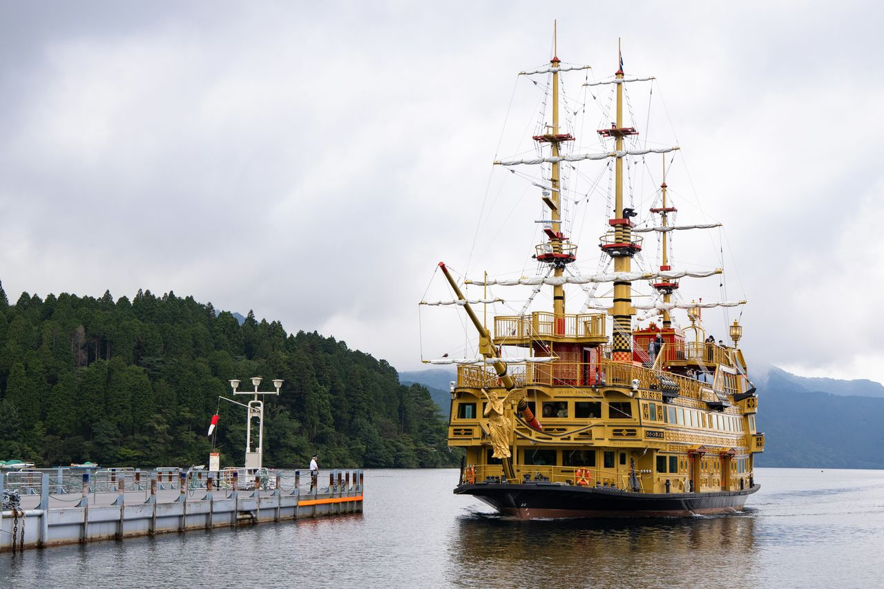 The Queen Ashinoko displays its goddess figurehead as it approaches the docks.