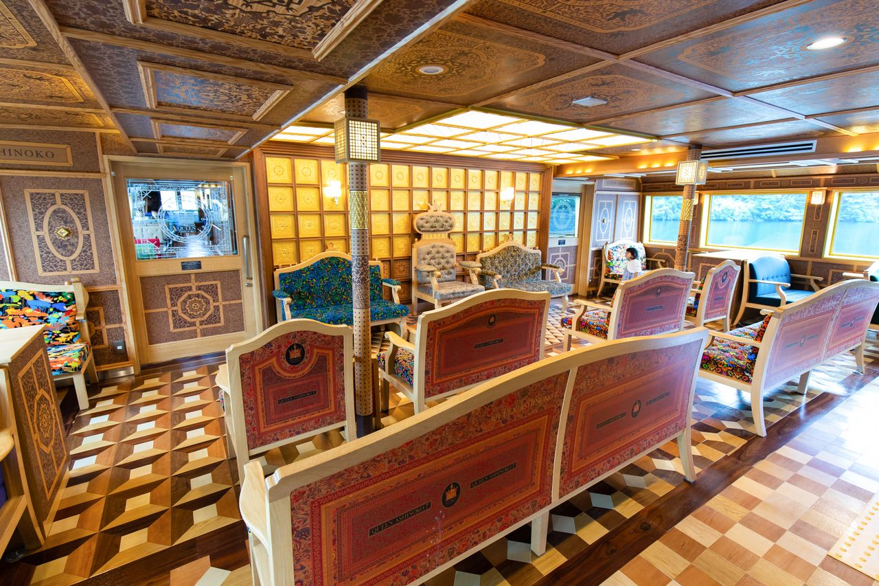 The first class cabin of the Queen Ashinoko boasts plush sofas and decorative woodwork, including a floor incorporating the traditional mosaic pattern of Hakone yosegi zaiku and  intricately patterned ceilings.