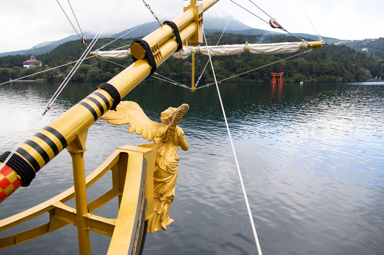 "The Queen Ashinoko glides across the lake surface. The popular ""peace gate"" at Hakone Shrine can be seen in the distance."