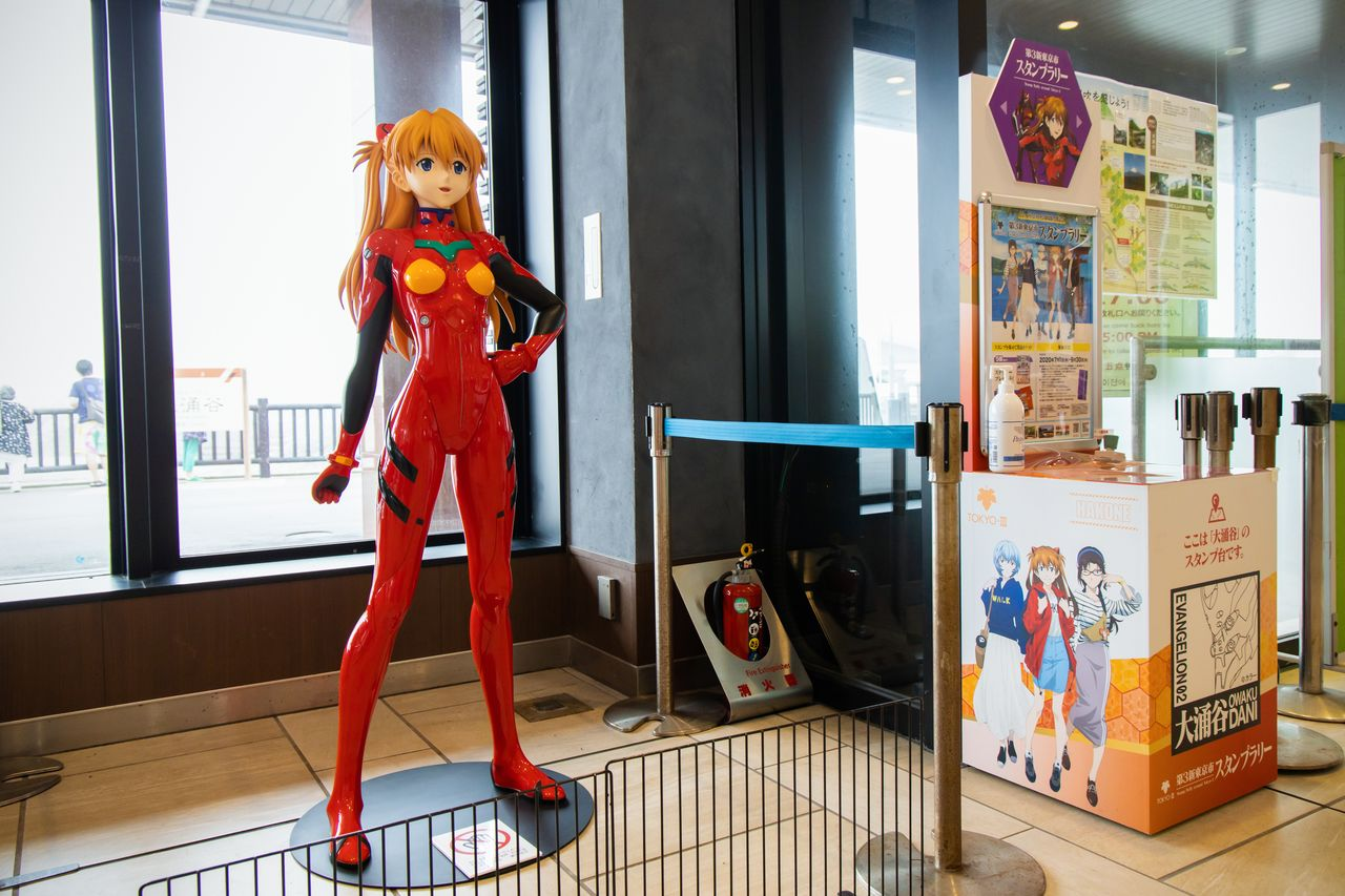 A life-size cutout of Evangelion character Shikinami Asuka Langley at Ōwakudani Station, alongside a stamp rally point.