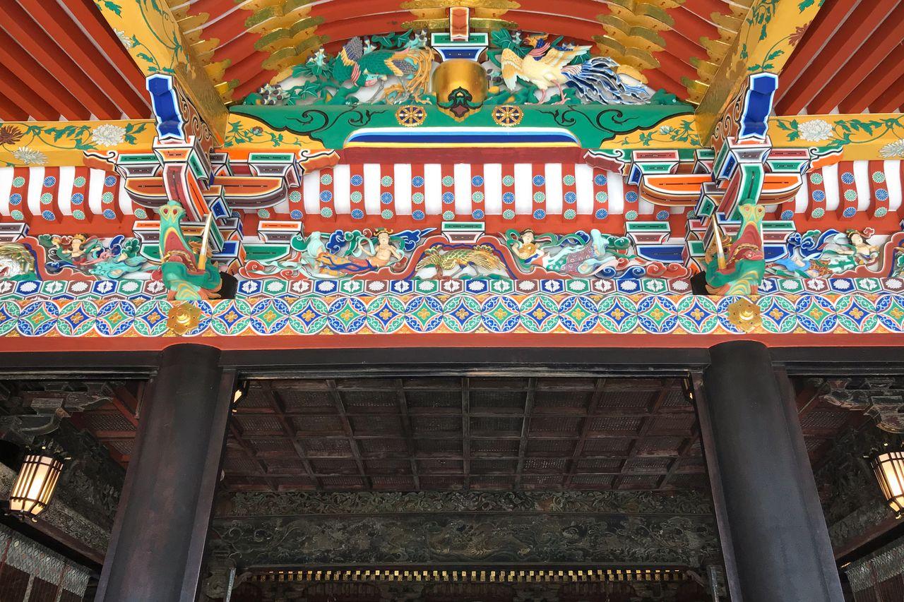 Rentang di bawah atap pelana setengah ujung di depan ruang ibadah dipenuhi dengan ukiran warna-warni. (Atas kebaikan Ōsaki Hachimangū)