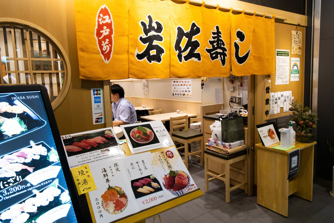 Iwasa-zushi secara mencolok menampilkan menu hidangan salmonnya di pintu masuk toko. (Foto oleh penulis)