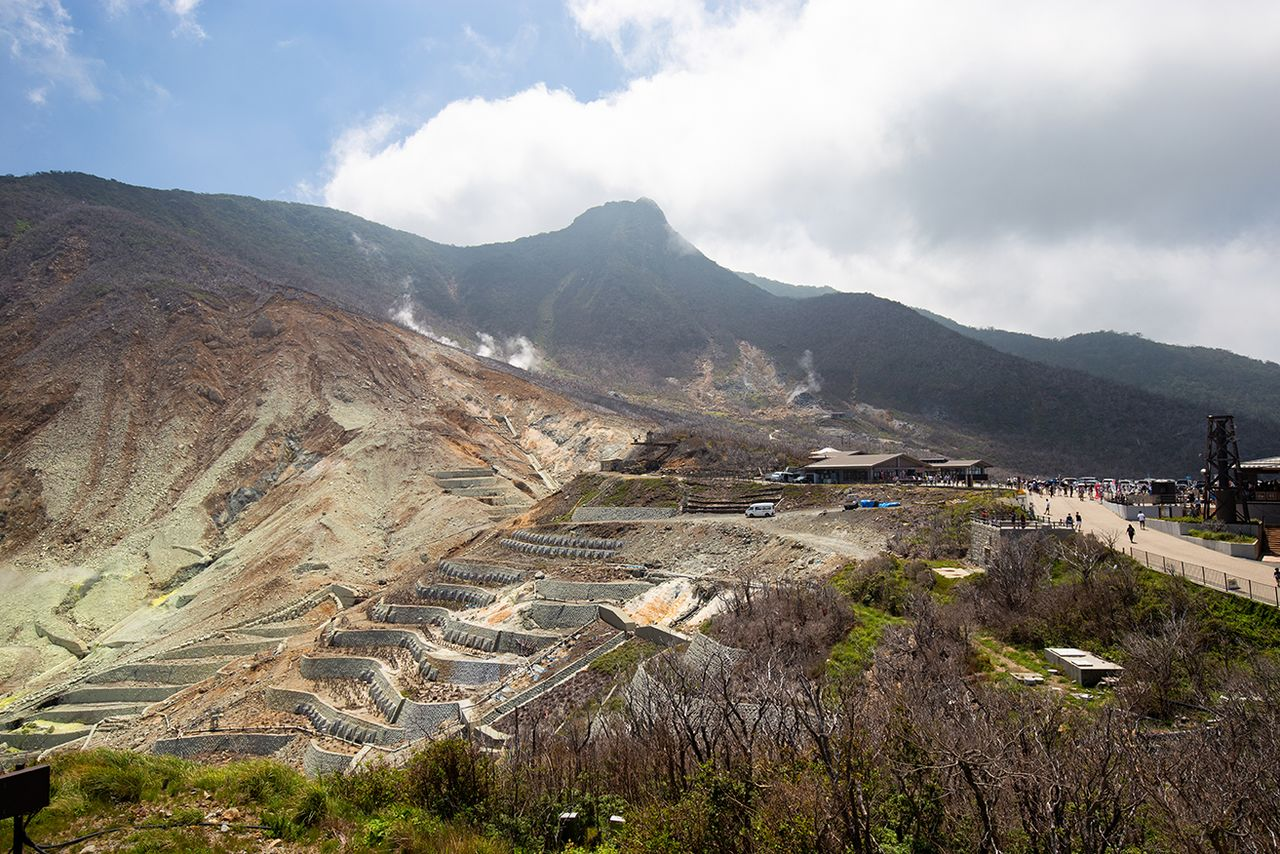 Ōwakudani and its steam vents with 1,409-meter Mount Kanmurigatake in the distance. Ōwakusawa at the left foreground is an area that is prone to landslides and is crisscrossed by containment structures.