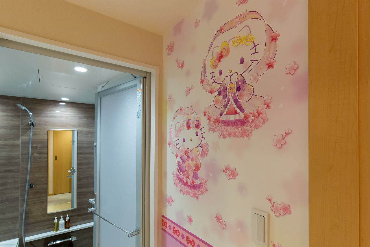 A Hello Kitty tennyo floats on the wall above the bathroom sink.