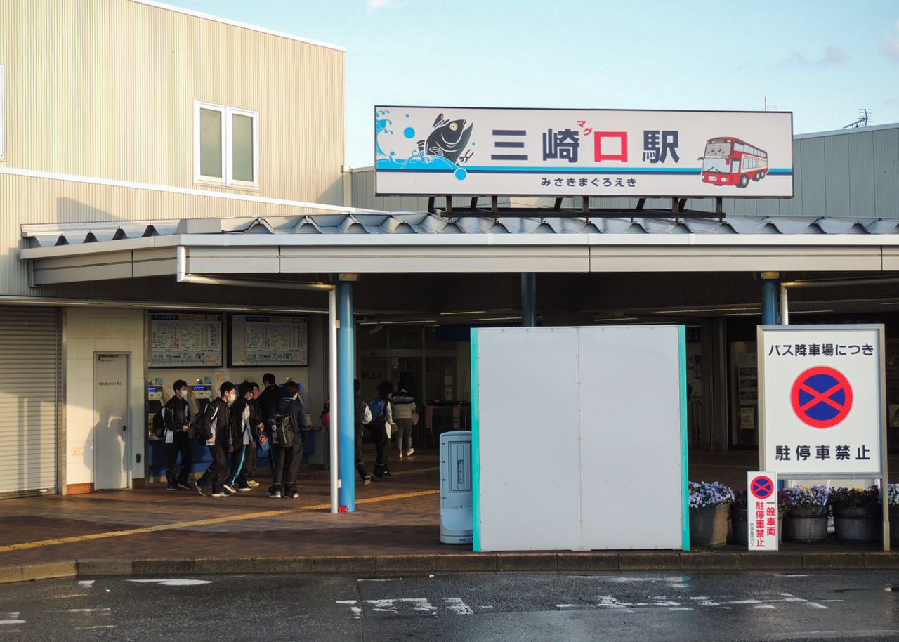 "The signboard for Misakiguchi Station contains red lettering written in phonetic hiragana script that changes the reading to ""Misaki Maguro Station"" (Misaki Tuna Station), a humorous nod to the port's fame as a base for tuna fishing. (Photo by the author)"