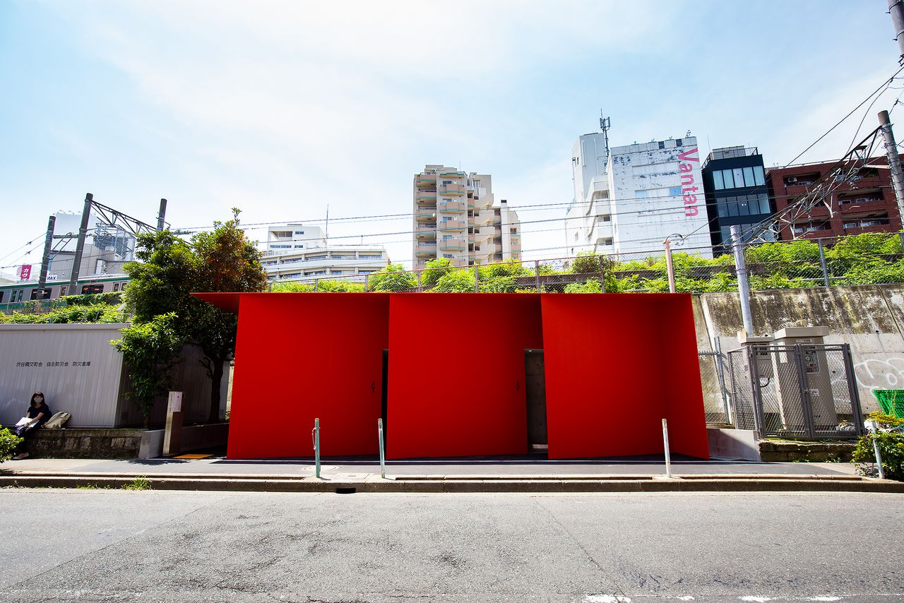 The red walls of the facility contrast the drab, jumbled surroundings.
