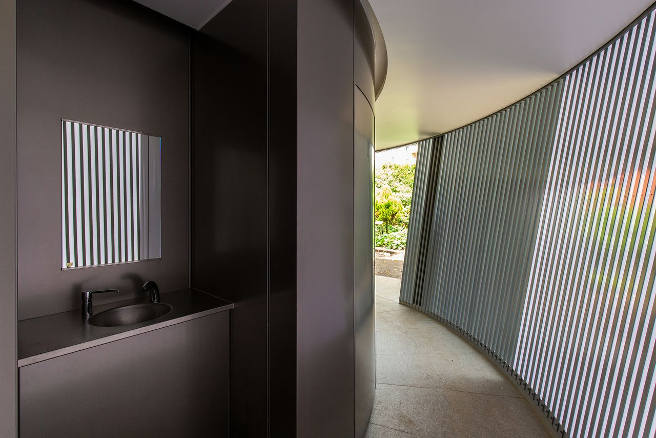 Slits in the outer wall allow in natural light. A sink is conveniently located along the passageway.