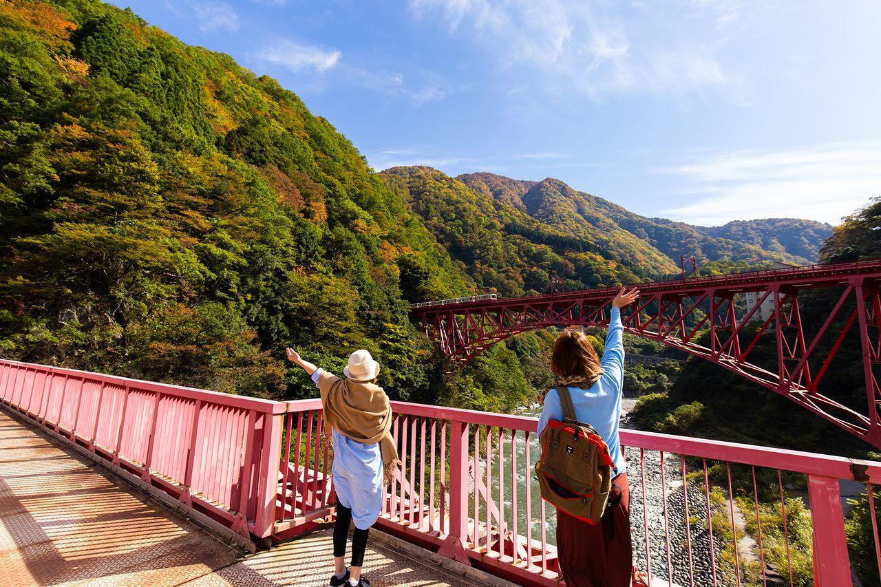 Para wisatawan melambai ke kereta yang melintasi Jembatan Shin-Yamabiko.