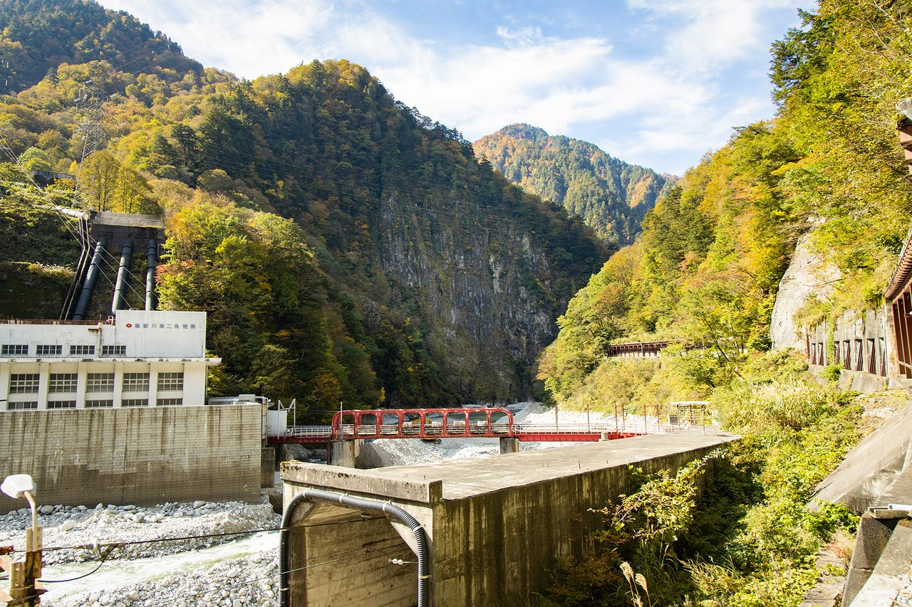 The 200-meter high cliff face of Nezumigaeshi looms beyond the red bridge at Kurobe Power Station No. 2.