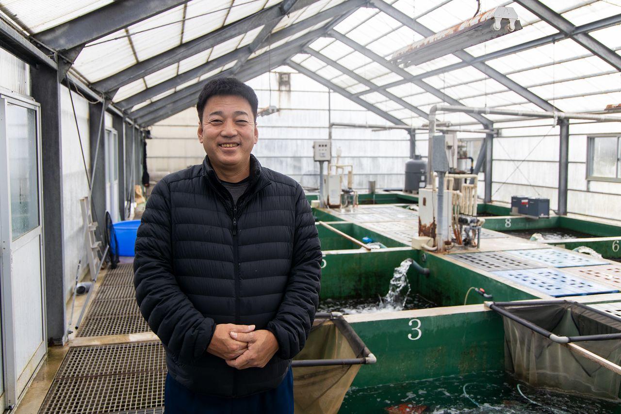 Isa Mitsunori dari Isa Koi Farms berdiri di dalam sebuah bangunan yang menampung tangki musim dingin.