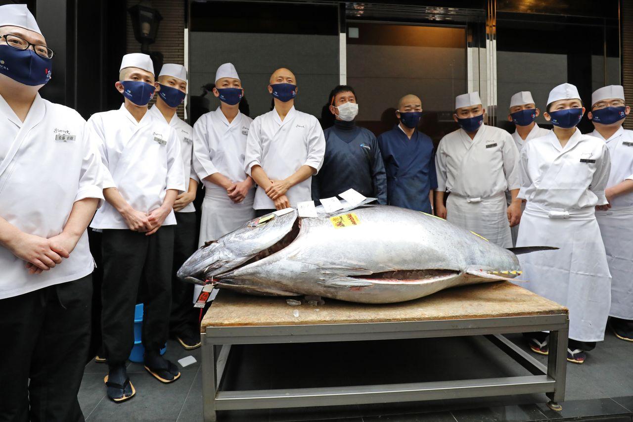 Pemilik Yamayuki Yamaguchi Yukitaka (warna biru di kanan tengah) di depan restoran sushi Ginza Onodera dengan tuna pertama di tahun baru. (© Jiji)