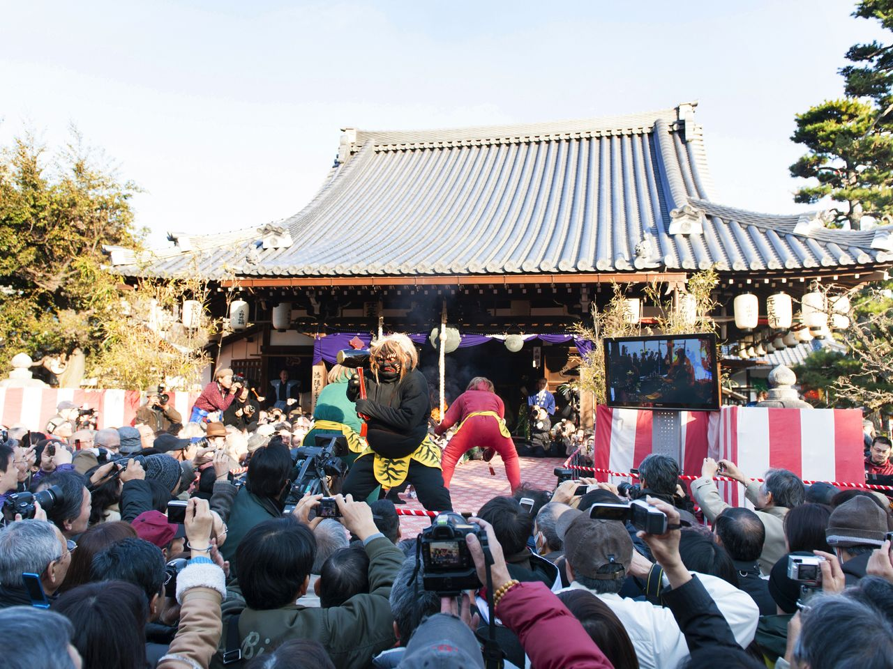 The stage where the <em>oni hōraku</em> ritual takes place is surrounded by eager crowds with their cameras.