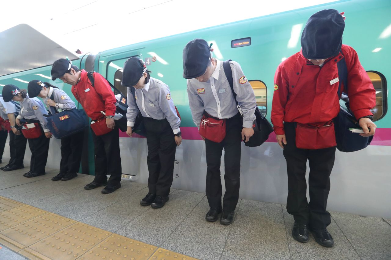 Shinkansen cleaning staff bow after tidying up a train. (© Jiji)