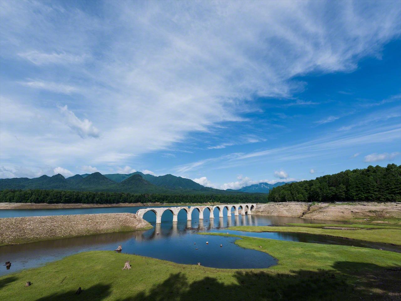 Jembatan itu menyatu dengan alam sekitarnya di bawah langit Juli yang jernih di Hokkaidō.