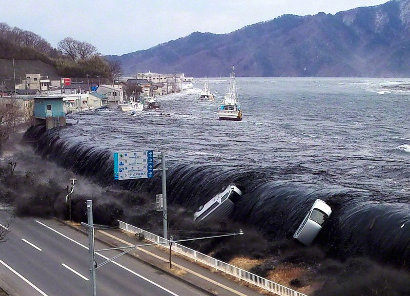 The tsunami crashes onto the shores of the city of Miyako. The cars swept up in the wave provide chilling testimony to the devastating power of the tsunami. (Image provided by a Miyako City employee.)
