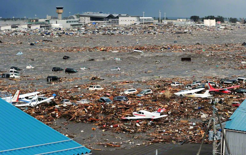 The tsunami swamps the runway at Sendai Airport. Cars and the shattered shells of houses litter the area. Light aircraft washed up by the tsunami float on a sea of refuse. In the background is the passenger terminal. The airport reopened for domestic flights on April 13.