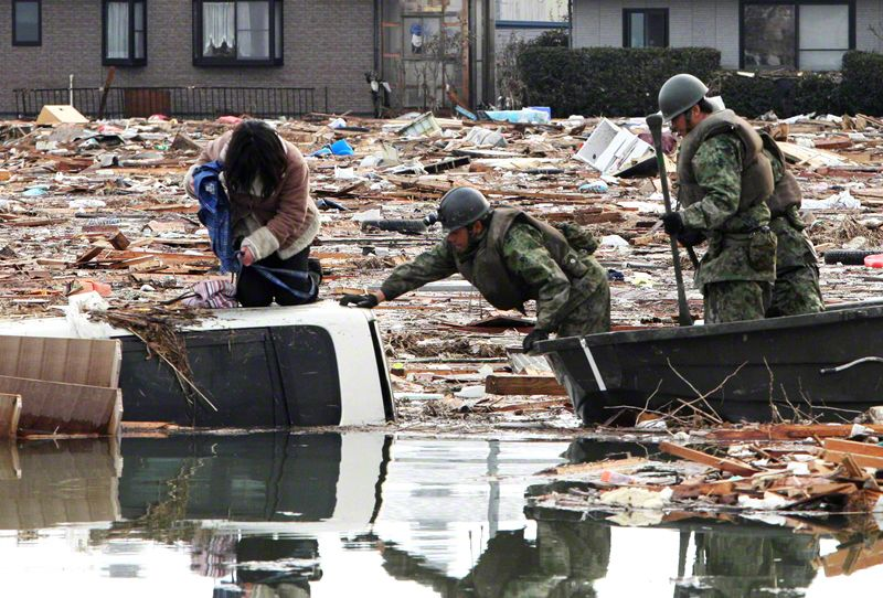 Self-Defense Force personnel use a boat to rescue a woman stranded on top of a car.