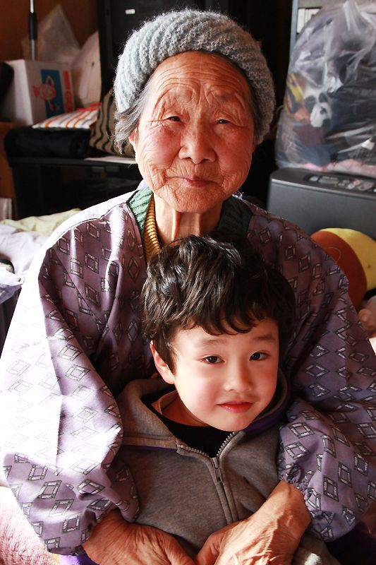 An elderly lady with her great-grandson. The whereabouts of the boy's father are still unknown.