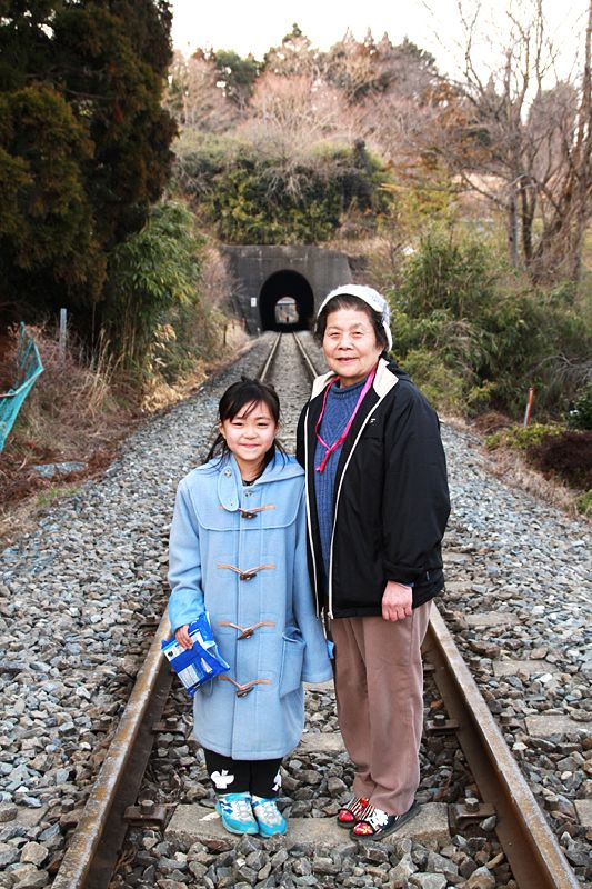 A mother and daughter stand on the railway tracks of the JR East Japan Kesennuma line, where no trains have run since the disaster.