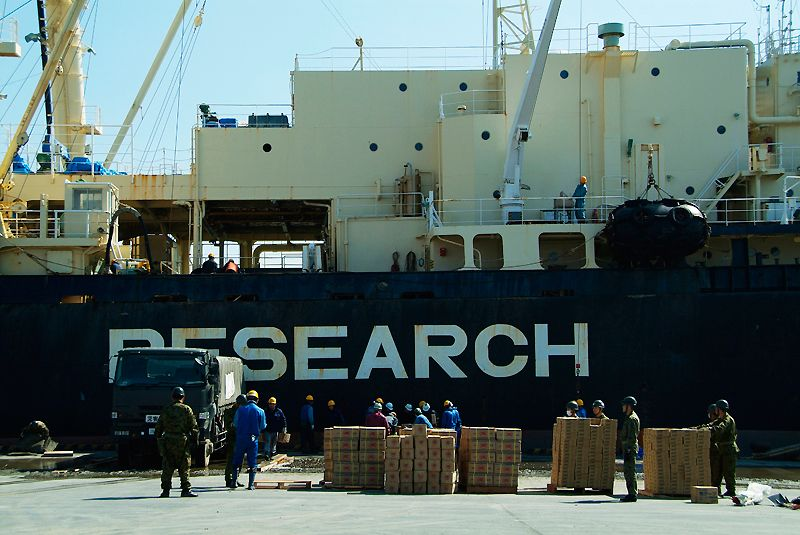 Large quantities of relief supplies are unloaded from a ship docked at the city's harbor.