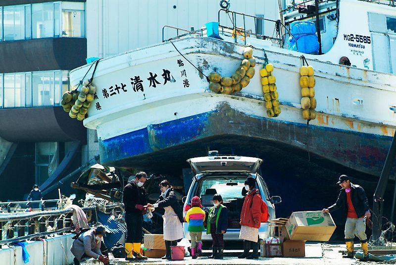A large fishing boat dumped onto a road by the powerful tsunami.