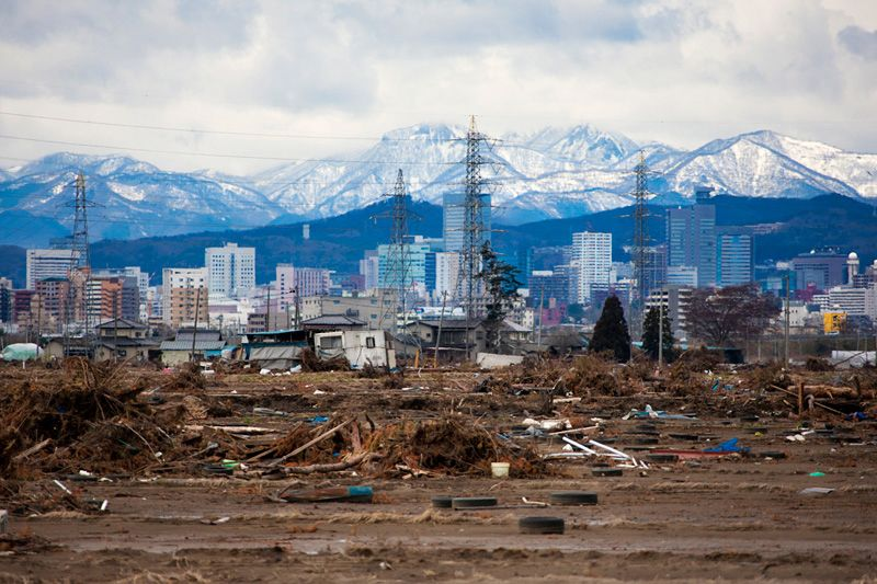 Debris from the tsunami was carried several kilometers inland from the sea. In the background, the city of Sendai and nearby mountains.