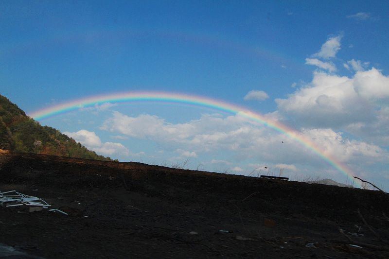 A crowd of local residents gathered to look up at this huge rainbow, which stretched right across the sky above the devastated town where everything was swept away.
